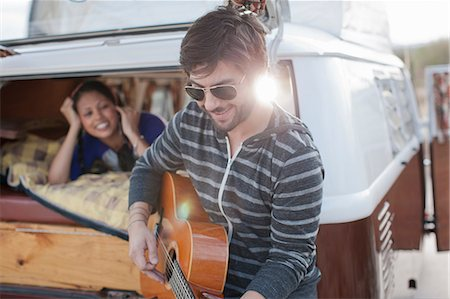Mid adult man playing guitar at back of camper van, smiling Stock Photo - Premium Royalty-Free, Code: 614-06896166