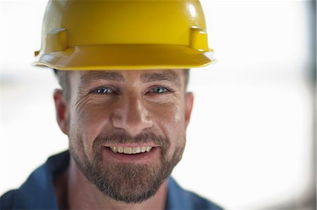 Mid adult construction worker wearing hard hat, smiling Stock Photo - Premium Royalty-Free, Code: 614-06896161