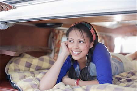 Young woman lying in the back of camper van, smiling Stock Photo - Premium Royalty-Free, Code: 614-06896163