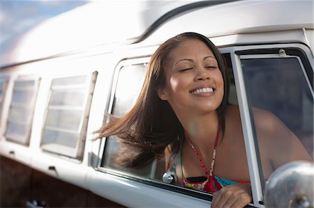 Young woman leaning out of the window of camper van, smiling Stock Photo - Premium Royalty-Free, Code: 614-06896179
