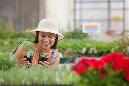 potted plant - Young woman looking at plants in garden centre, smiling Stock Photo - Premium Royalty-Free, Code: 614-06896187