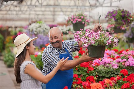 Mature man serving young woman in garden centre, smiling Stock Photo - Premium Royalty-Free, Code: 614-06896182