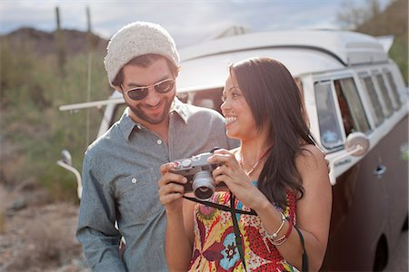 road trip - Young woman holding camera with boyfriend on road trip, smiling Stock Photo - Premium Royalty-Free, Code: 614-06896199