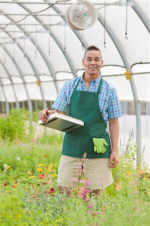 Mature man holding clipboard in garden centre, portrait Stock Photo - Premium Royalty-Free, Code: 614-06896281
