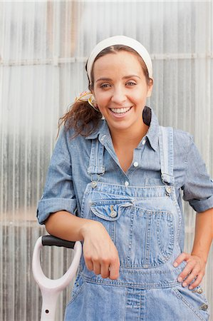 Young woman in dungarees leaning on spade in garden centre, portrait Stock Photo - Premium Royalty-Free, Code: 614-06896323