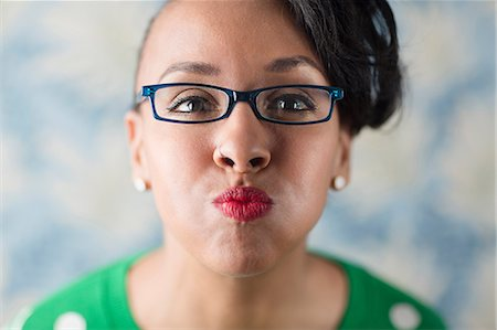 Close up portrait of woman puckering her lips Stock Photo - Premium Royalty-Free, Code: 614-06896553