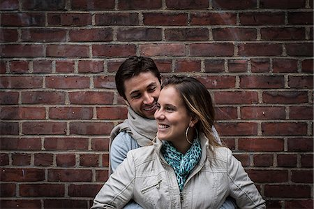 Portrait of smiling couple in front of brick wall Stock Photo - Premium Royalty-Free, Code: 614-06896561