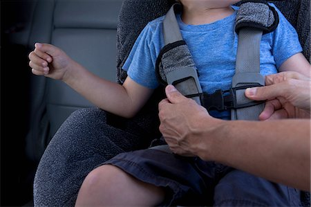 dependable - Mother fastening child safety seat belt in car Stock Photo - Premium Royalty-Free, Code: 614-06896679