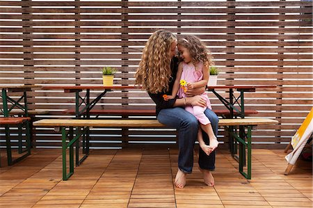 people sitting on bench - Mother and daughter sitting on bench on patio Stock Photo - Premium Royalty-Free, Code: 614-06896697