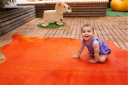 Baby girl crawling on orange rug, portrait Stock Photo - Premium Royalty-Free, Code: 614-06896707