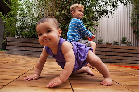 Baby girl crawling on patio, brother in background Stock Photo - Premium Royalty-Free, Code: 614-06896708