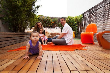 Family sitting on patio with baby girl crawling in foreground Stock Photo - Premium Royalty-Free, Code: 614-06896709