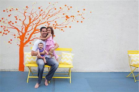 people sitting on bench - Father with two daughters in front of tree mural on wall Stock Photo - Premium Royalty-Free, Code: 614-06896701