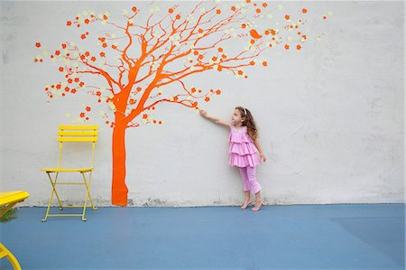 Girl pointing to orange tree mural on wall Stock Photo - Premium Royalty-Free, Code: 614-06896702