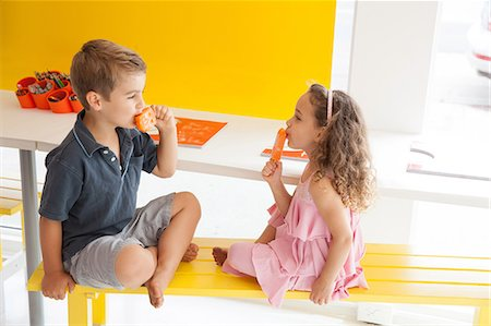 Brother and sister eating ice lollies on bench indoors Stock Photo - Premium Royalty-Free, Code: 614-06896714