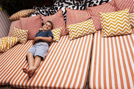 Boy relaxing on striped outdoor  furniture with cushions Stock Photo - Premium Royalty-Free, Code: 614-06896711