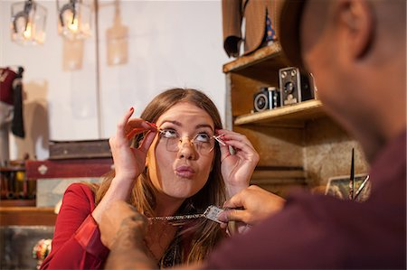 Woman in vintage shop trying on glasses and pulling faces Stock Photo - Premium Royalty-Free, Code: 614-06896725