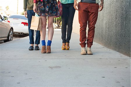 Four young adults standing on pavement, low section Stock Photo - Premium Royalty-Free, Code: 614-06896743