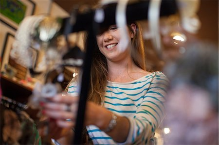 selecting - Young woman looking through clothes rail in vintage shop Stock Photo - Premium Royalty-Free, Code: 614-06896758
