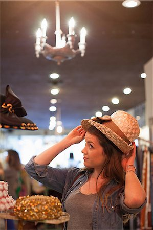 Young woman trying on straw hat in vintage shop Stock Photo - Premium Royalty-Free, Code: 614-06896767
