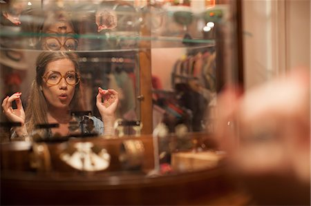 Young woman trying on glasses and pulling faces in vintage shop Stock Photo - Premium Royalty-Free, Code: 614-06896769
