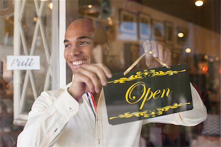 small business - Shopkeeper turning open sign on vintage shop door Stock Photo - Premium Royalty-Free, Code: 614-06896770