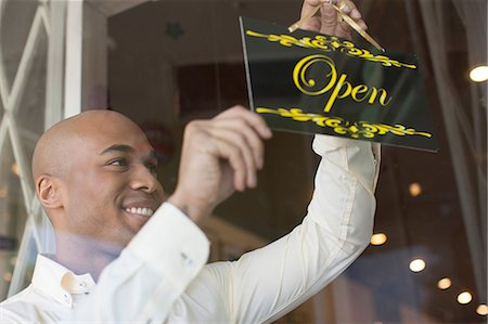 Shopkeeper turning open sign on vintage shop door Stock Photo - Premium Royalty-Free, Code: 614-06896771