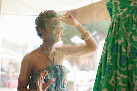 desire - Young woman looking at dress through shop window Stock Photo - Premium Royalty-Free, Code: 614-06896781