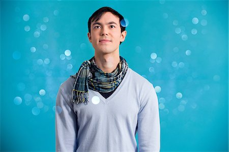 sparkling - Portrait of young man wearing blue jumper and scarf Stock Photo - Premium Royalty-Free, Code: 614-06896859