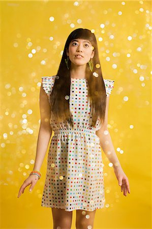 Portrait of young woman wearing spotted dress with glitter Stock Photo - Premium Royalty-Free, Code: 614-06896877