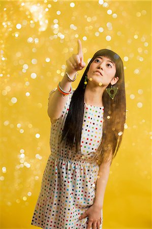 Portrait of young woman wearing spotted dress with glitter Stock Photo - Premium Royalty-Free, Code: 614-06896878