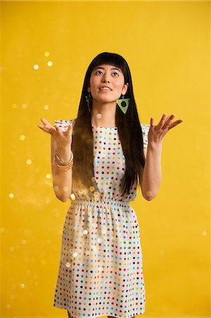 sparkling - Portrait of young woman wearing spotted dress catching glitter Stock Photo - Premium Royalty-Free, Code: 614-06896879
