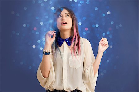 Portrait of young woman looking up at glitter Stock Photo - Premium Royalty-Free, Code: 614-06896871