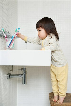 Girl toddler on tiptoe reaching over bathroom sink Stock Photo - Premium Royalty-Free, Code: 614-06896917