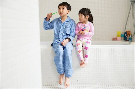Brother and sister sitting on edge of bath with toothbrushes Stock Photo - Premium Royalty-Free, Code: 614-06896919