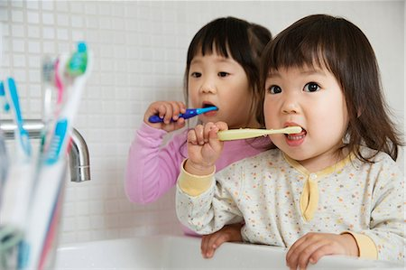 Two girl toddlers brushing teeth at bathroom sink Stock Photo - Premium Royalty-Free, Code: 614-06896911