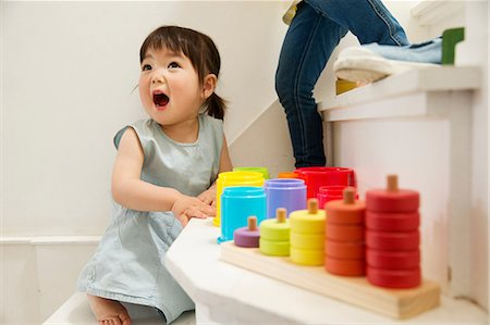 Female toddler playing with toys on staircase Stock Photo - Premium Royalty-Free, Code: 614-06896925