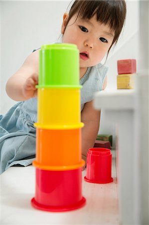 Female toddler on stairs building colorful tower Stock Photo - Premium Royalty-Free, Code: 614-06896926