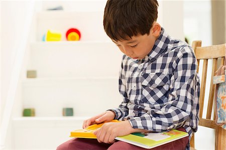 Young boy sitting on chair studying game Stock Photo - Premium Royalty-Free, Code: 614-06896929