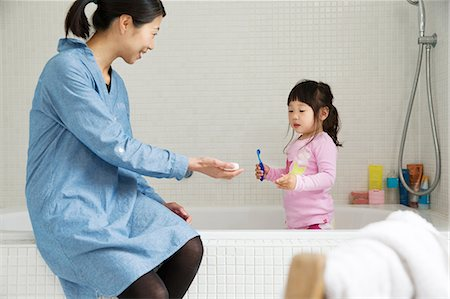 Mother with female toddler standing in bath with tooth brush Stock Photo - Premium Royalty-Free, Code: 614-06896921