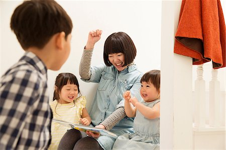 focus on background - Mother and children laughing at storybook Stock Photo - Premium Royalty-Free, Code: 614-06896934