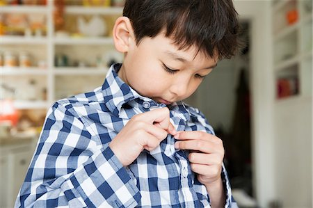 Close up portrait of young boy fastening shirt buttons Stock Photo - Premium Royalty-Free, Code: 614-06896935