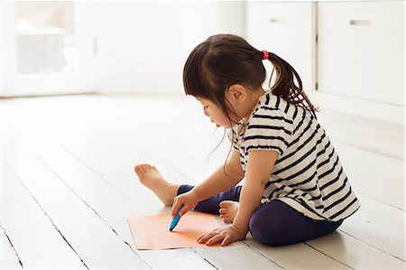 Female toddler sitting on floor drawing Stock Photo - Premium Royalty-Free, Code: 614-06896942