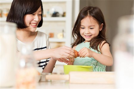 east asian - Mother and young daughter cracking egg into mixing bowl Stock Photo - Premium Royalty-Free, Code: 614-06896959