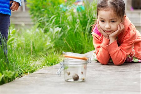 Young girl in garden watching jar of snails Stock Photo - Premium Royalty-Free, Code: 614-06896969