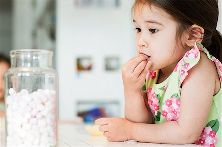 Close up of young girl tasting marshmallows Stock Photo - Premium Royalty-Free, Code: 614-06896963