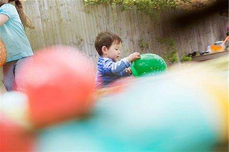 Male toddler playing in garden with balloon Stock Photo - Premium Royalty-Free, Code: 614-06896975