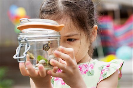 Young girl studying jar of snails Stock Photo - Premium Royalty-Free, Code: 614-06896971