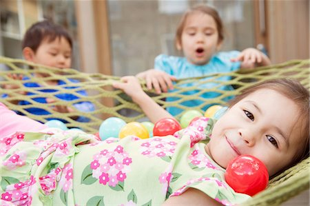 Portrait of young girl in hammock with colored balls Stock Photo - Premium Royalty-Free, Code: 614-06896973