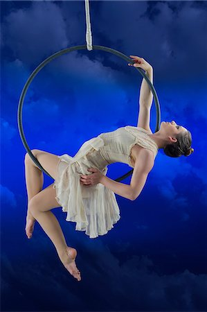 flexible (people or objects with physical bendability) - Aerialist performing on hoop against blue background Stock Photo - Premium Royalty-Free, Code: 614-06897004